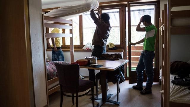 Drei Asylsuchende in einem kleinen Zimmer mit Kajütenbetten.