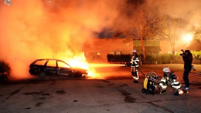 Feuerwehrmänner löschen ein brennendes Auto in Stockholm.
