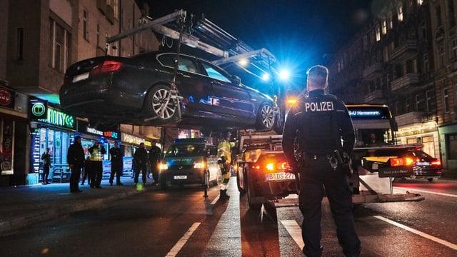 Nächtliche Szene. Ein fetter BMW wird mit einem Ladekran hochgehoben. Ein Polizist schaut zu.
