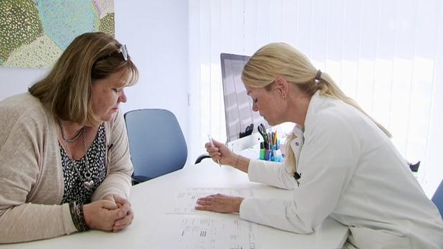 Die Patientin sitzt mit ihrer Ärztin am Besprechungstisc über ein Papier gebeugt.