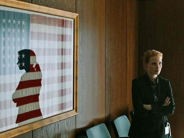 Die Schauspielerin spiegelt sich in der Glasscheibe einer eingerahmten Amerikanischen Flagge.