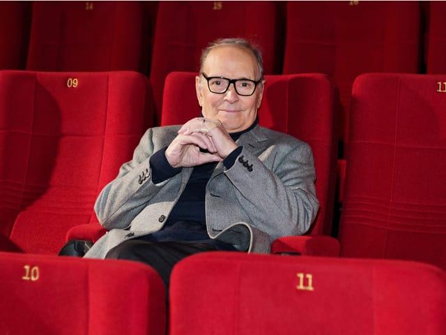 Ennio Morricone sitzt in einem Kino mit roten Sesseln.