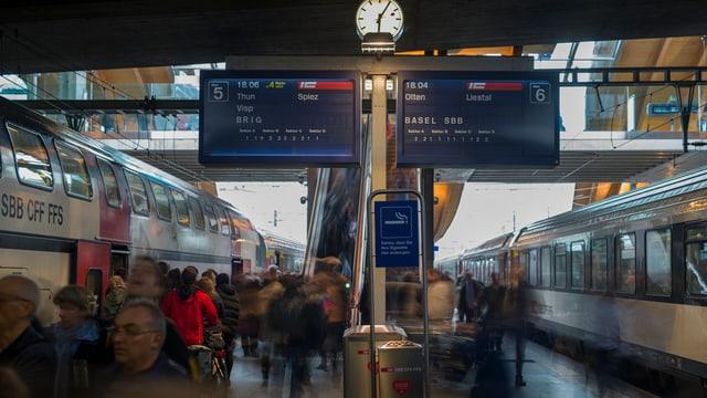 Passagiers che ascendan e descendan ils trens a la staziun da Berna.