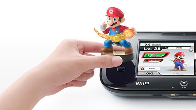 Eine Hand hält eine Amiibo-Figur auf den Wii-U-Kontroller.