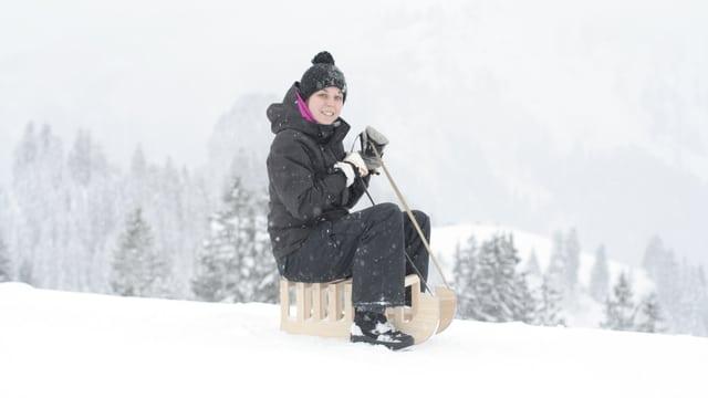Die Produktedesignerin Christa Rüetschi auf ihrer modernen Adaption des klassischen Schlittens «Küttiger Frosch».