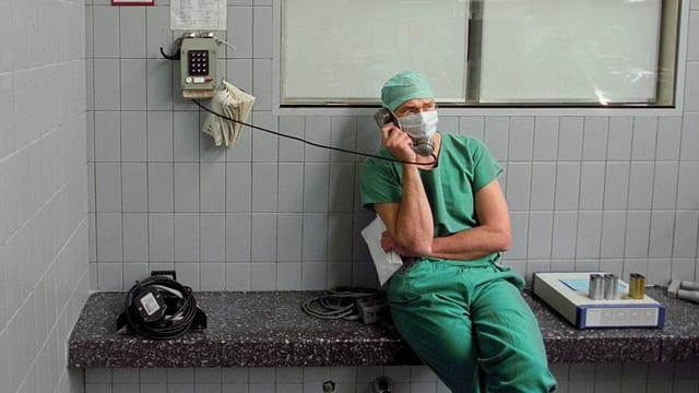 Mann mit grünem Arztkittel sitzt vor Operationssaal am Telefon.