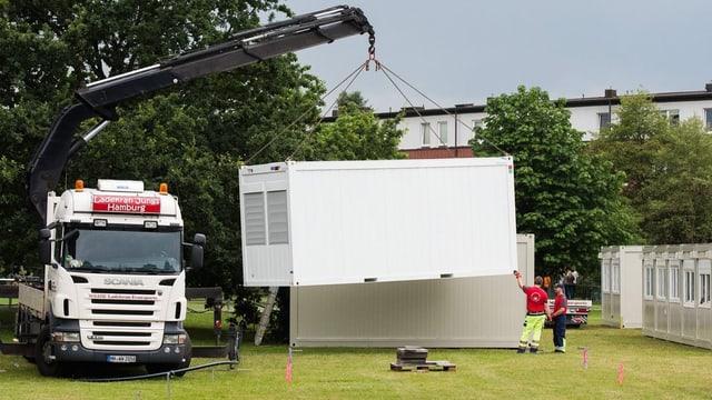 Kranlastwagen ladet Wohncontainer ab