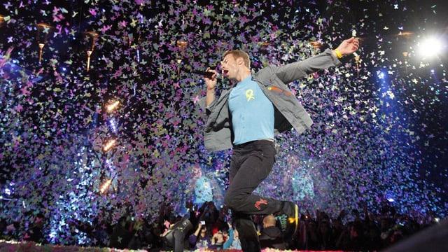 Ein Mann singt auf einer Bühne, vom Himmel regnen bunte Konfetti.