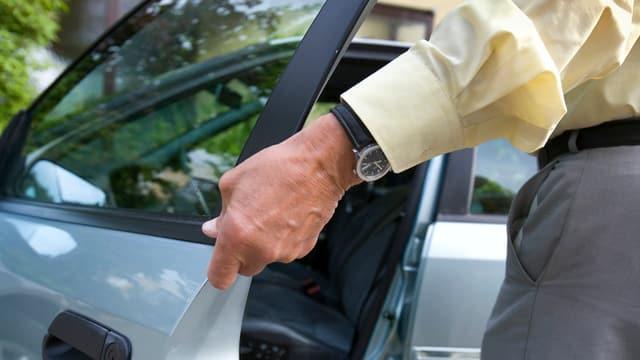Ein älterer Mann öffnet eine Autotüre.