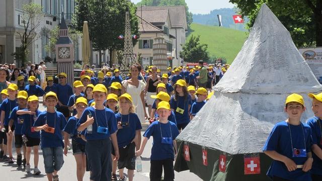 Kinder in blauen T-Shirts und gelben Hütchen ziehen durch Herisau.
