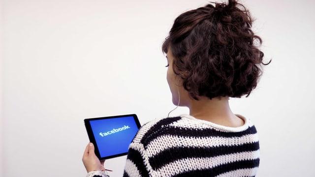 Eine Frau hat Kopfhörer im Ohr, auf dem Bildschirm das Facebook-Logo.