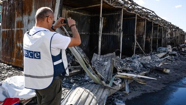 Ein OSZE-Beobachter fotografiert Bombenschäden in Donezk.