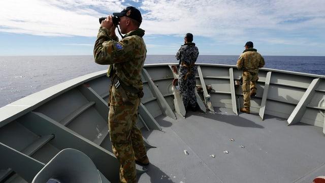 Männer mit Feldstecher schauen vom Schiff aufs Meer.