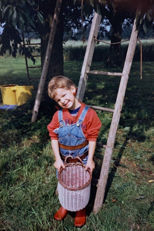 Monika Erni als Kind unter einem Kirschen Baum