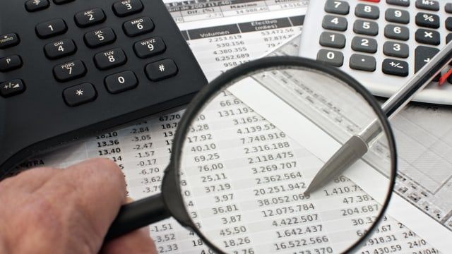 Mann mit Lupe schaut auf Blatt mit Zahlen