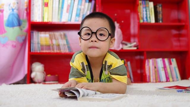 Ein Bub mit Brille liest in einem Buch.
