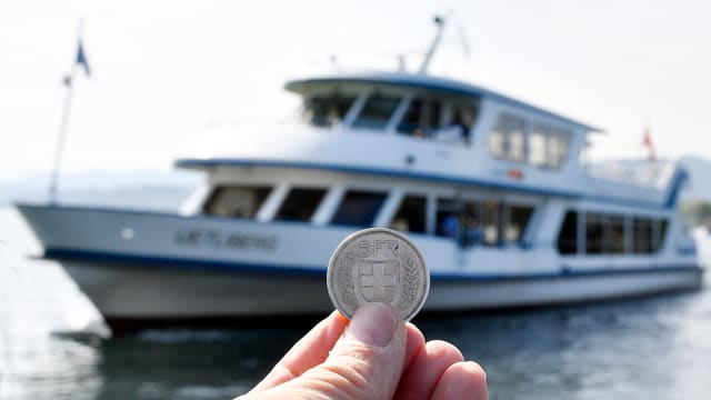 Eine Hand hält eine Fünf-Franken-Münze vor einem Schiff in die Kamera.