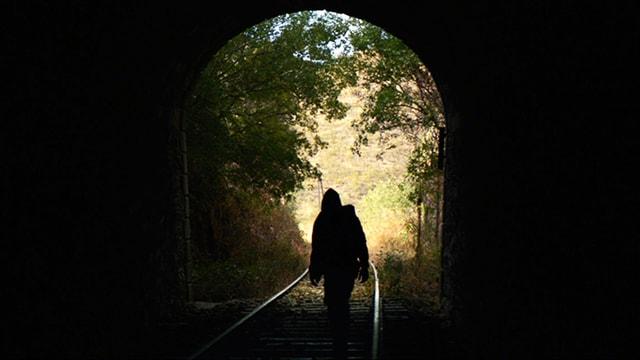 Schattengestalt geht auf Tunnelöffnung zu.