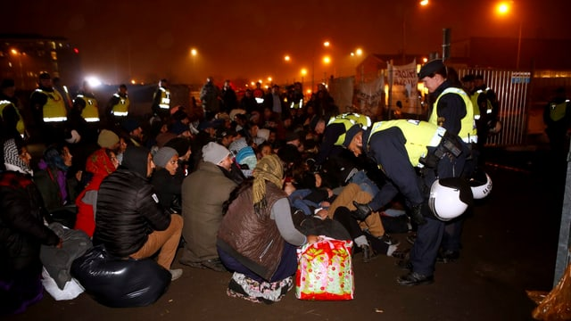 Flüchtlinge sitzen am Boden, Polizisten reden mit ihnen