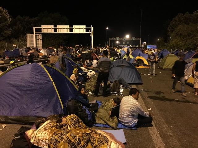 Flüchtlinge sitzen auf der Strasse. Es ist Nacht. Viele Zelten sind aufgespannt.