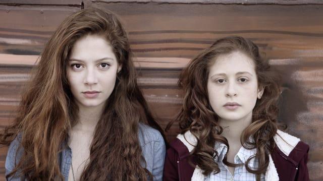 Zwei Schwestern aus der Serie blicken in die Kamera.