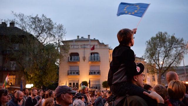 In uffant cun ina bandiera da l'UE durant ina manifestaziun a Budapest.