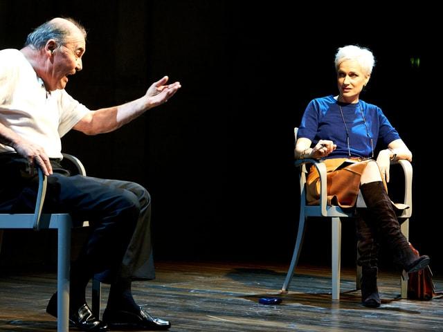 Mann und Frau sitzen auf Stühlen auf Bühne