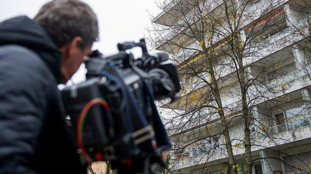 Ein Kameramann filmt ein Mehrfamilienhaus