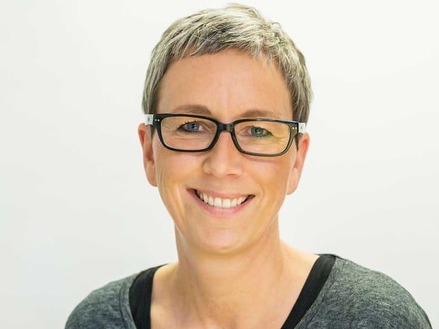 Eine Frau mit einem Kurzhaarschnitt und Brille.