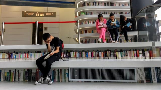 Drei junge Frauen sitzen nebeneinander in einer Bibliothek auf einer Bank und lesen.