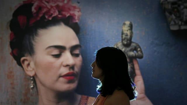 Frau schaut über den linken Bildrand heraus, im Hintergrund ein grosses Abbild von Frida Kahlo.