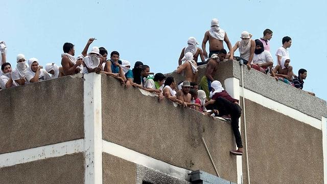 Teilweise vermummte Männer auf einem Hausdach.