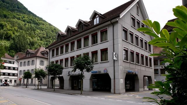 Bankgebäude an einer Strasse im Hintergrund weitere Häuser und Berge.