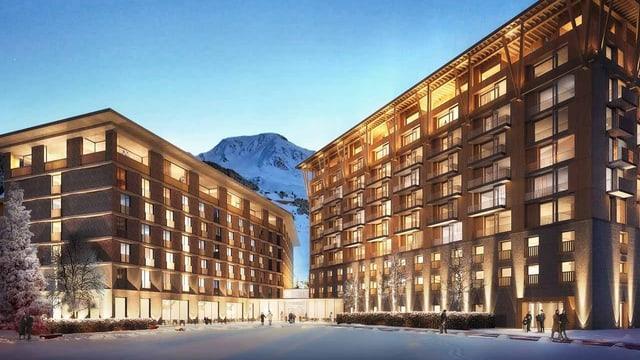 Zwei grosse, beleuchtete Gebäude vor einem Berg.