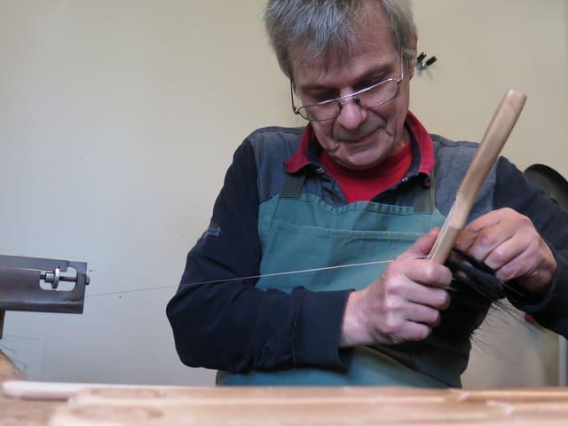Mann mit Brille bindet Bürste.