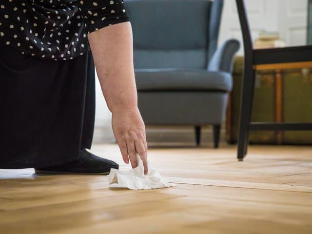 Eine Frau liest ein Tauschentuch vom Boden auf, dahinter steht ein grauer Sessel.