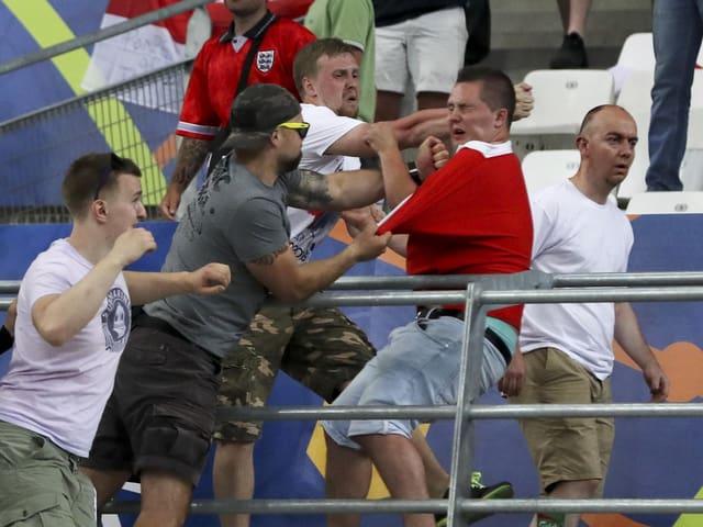 Zwei russische Fans attackieren einen englischen Fan.