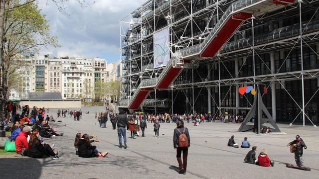 Ina colona da glieud spetga per entrar en il Centre Pompidou. Blera glieud sesa sin il plaz e mira per las arias.