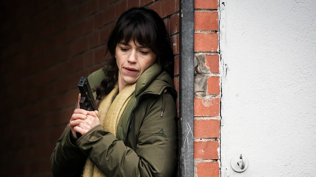 Eine Frau hält eine Pistole und lehnt an einer Hausmauer