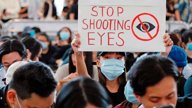 Junge Frau hält ein Schild in die Höhe auf dem steht: Zielt nicht in die Augen.