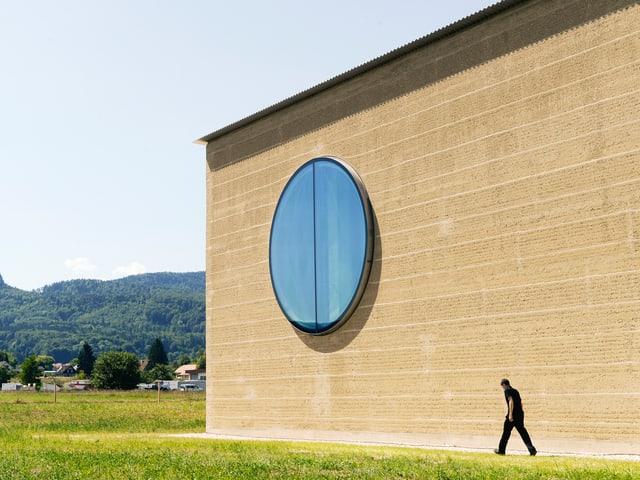 Schlichtes Lehmhaus mit einem grossen, runden Fenster.