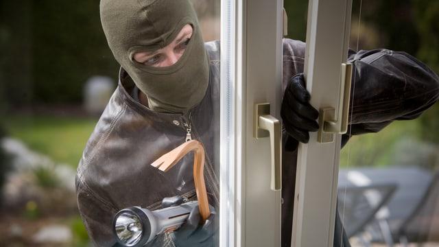 Ein vermummter Einbrecher bricht ein Fenster auf.