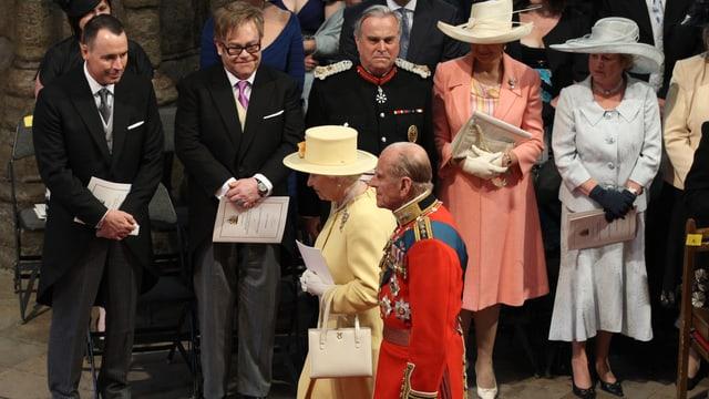 Elton John und weitere Eingeladene stehen bei einem Auftritt der Queen und Prinz Philip Spalier.