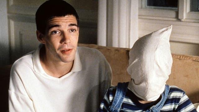 Ein junger Mann mit einem weissen Pullover sitzt auf einem Sessel, neben ihm ein Junge mit einem über den Kopf gestülpten Sack.