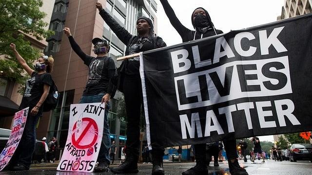 Purtret da quatter persunas che defendan il logo «Black lives matter».