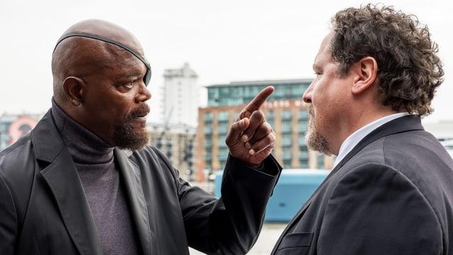 Zwei Männer stehen sich gegenüber. Der Mann links trägt eine Augenklappe und deutet mit dem Finger auf den Mann rechts.