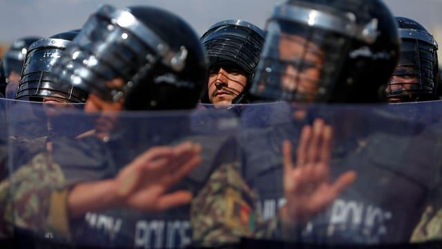 Militärpolizisten stehen in einer Reihe und halten Schilde hoch