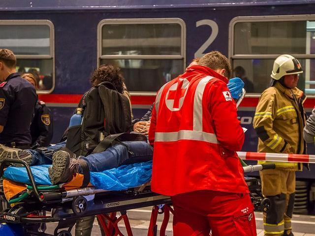 Sanitäter, verletzte Person auf einer Bahre liegend.