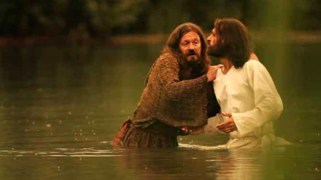 Eine nachgestellten Szene zeigt Jesus in einem weissen Gewand, wie er in einem Teich steht, neben ihm ein Mann, der ihn um die Schulter greift.