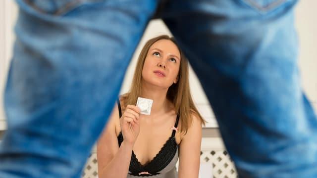 Eine Frau sitzt auf dem Bett, vor ihr steht ein Mann. Sie hält ein Kondom in der Hand und hält es ihm hin.